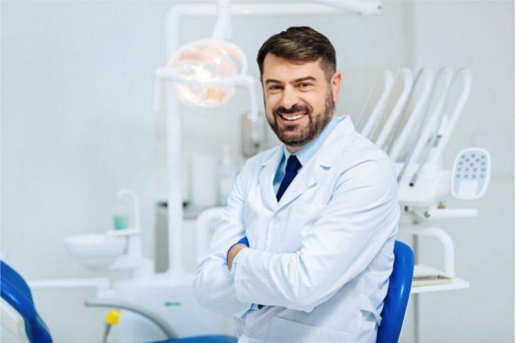 Dentista frente em pé no consultório