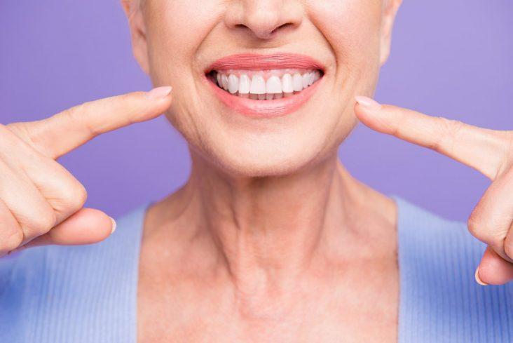 Mulher idosa sorrindo apontando para boca