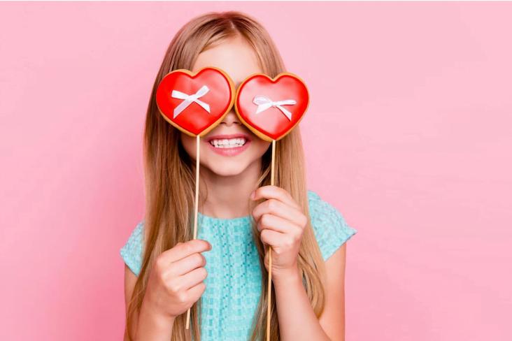 Menina sorrindo segurando pirulitos formato coração em frente aos olhos